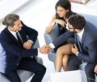 Handshake Manager and the client sitting in the office lobby. In front of the open laptop Stock Photos
