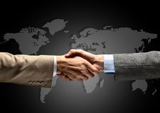 Handshake with map of the world. In background Royalty Free Stock Image