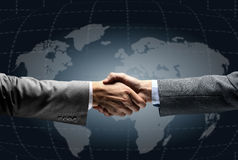 Handshake with map of the world in. Background stock image