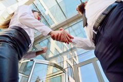 Handshake of a man and a woman against a multi-storey office building. Make a deal. Friendly relations. Office staff stock photo