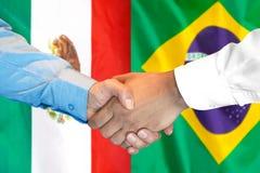 Handshake on Mexico and Brazil flag background. Business handshake on the background of two flags. Men handshake on the background of the Mexico and Brazil flag royalty free stock image