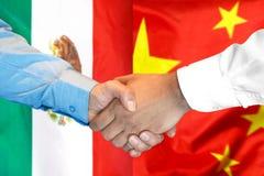 Handshake on Mexico and China flag background. Business handshake on the background of two flags. Men handshake on the background of the Mexico and China flag stock photography