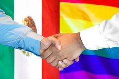 Handshake on Mexico and LGBT gay flag background. Business handshake on the background of two flags. Men handshake on the background of the Mexico and LGBT gay stock image