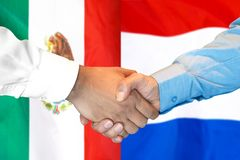 Handshake on Mexico and Netherlands flag background. Business handshake on the background of two flags. Men handshake on the background of the Mexico and Dutch stock image