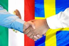 Handshake on Mexico and Sweden flag background. Business handshake on the background of two flags. Men handshake on the background of the Mexico and Sweden flag royalty free stock images