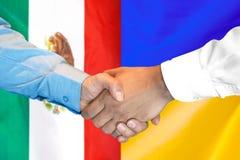 Handshake on Mexico and Ukraine flag background. Business handshake on the background of two flags. Men handshake on the background of the Mexico and Ukraine royalty free stock photography