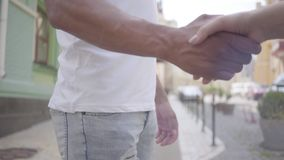 Handshake of middle eastern man and caucasian woman in front of city background close-up. Love, friendship, the romantic. Hands middle eastern man and caucasian stock video