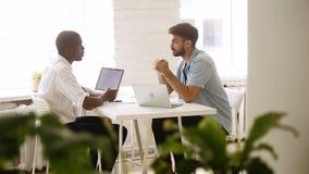 Handshake multirazziale dei partner che fa buon affare nell'ufficio accogliente del sottotetto archivi video