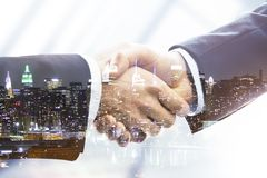 Handshake. On night city background, double exposure Royalty Free Stock Images