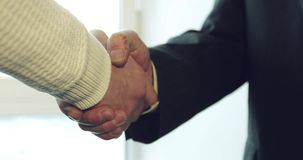 Handshake of an old man with a rough, scratched hand with a young businessman. Business partners handshaking stock footage