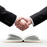 Handshake and book Royalty Free Stock Image