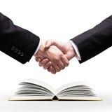 Handshake and book Royalty Free Stock Image