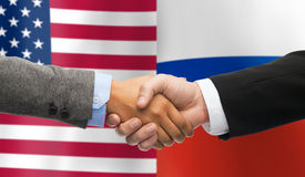 Handshake over american and russian flags. Partnership, politics, gesture and people concept - close up of handshake over american and russian national flags stock photo