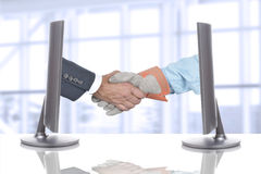 Handshake Over Desk in Business Office Stock Images