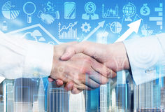 A handshake is over the growing arrow and business icons . Stock Photo