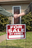 Handshake over home for sale sign. Showing real estate transaction Royalty Free Stock Images