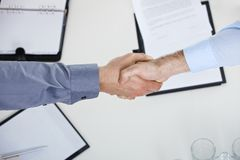 Handshake over meeting table Royalty Free Stock Photos