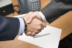 Handshake over paper Royalty Free Stock Image