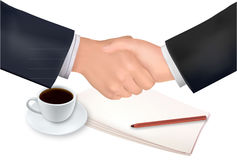 Handshake over paper and coffee. Royalty Free Stock Image
