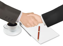 Handshake over paper and pen. Stock Image