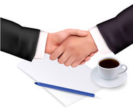 Handshake over paper and pen. Royalty Free Stock Image