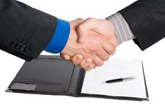 Handshake over paper and pen Royalty Free Stock Images