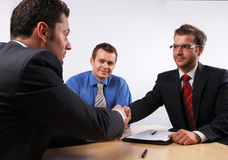 Handshake over signed cotract. Three businessmen sitting at a table negotiating and signing a contract. handskake stock images
