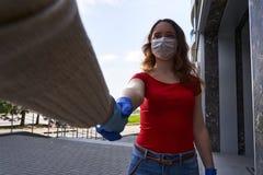 Handshake of people in latex gloves against COVID-19 coronavirus epidemic in quarantine outdoors, girl in protective mask