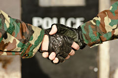 Handshake police. Two men shaking hands on the background of a police shield Stock Images