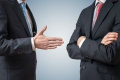 Handshake refuse. Man is refusing shake hand with businessman who is offering his hand. stock images