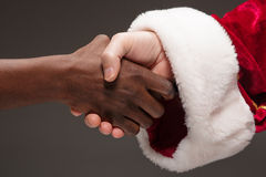 The handshake of Santa Claus and african man Royalty Free Stock Images
