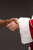 The handshake of Santa Claus hand and hand of african man Royalty Free Stock Photography