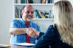 Handshake of senior businessman and woman after job interview stock image