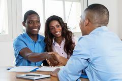 Handshake after signing contract with real estate agent. Handshake after signing contract with african american real estate agent at new home stock photography
