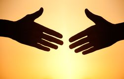 Handshake at sunset. Two arms stretching towards each other to shake against the sunset Stock Photos
