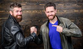 Handshake symbol of successful deal. Approved business deal. Handshake gesture meaning. Have agreed. Brutal bearded men. Wear leather jackets shaking hands stock photography