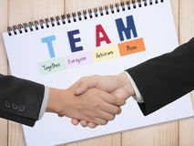 Handshake on TEAM background 1. Handshake of two business mans waring black suit on word spell TEAM on white notebook Teamwork concept Royalty Free Stock Image