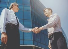 Handshake of Two Beautiful Businessmen Against Royalty Free Stock Photo