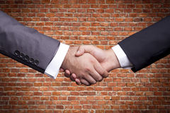 Handshake. Two businessman handshaking front of the brick wall Stock Photography