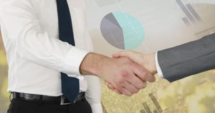 Handshake between two businessmen 4k. Close up of a handshake between two businessmen with digital animation of graphs and statistics running in  the background stock video