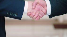 Handshake between two businessmen. Young guy buying a car from a dealer. Handshake between buyer and seller. Handshake between two businessmen businesspeople stock video footage