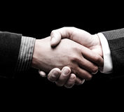 Handshake of two leaders over black background. Handshake of two men leaders over black background Royalty Free Stock Photo