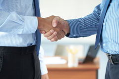 Handshake, two male hands both wear blue shirts Royalty Free Stock Photography