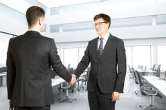 Handshake of two men in a bright modern office Royalty Free Stock Images