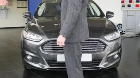 Handshake of two men on new car background. Close up of men greeting with handshake. Business partners handshaking. Handshake of two men on new car background stock video footage
