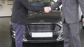Handshake of two men on new car background. Close up of men greeting with handshake. Business partners handshaking. Handshake of two men on new car background stock video