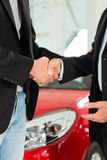 Handshake of two men in suits with a red car Stock Photos