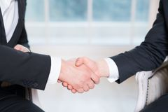 Handshake of two people, businessmen on a light background. Handshake of two people, businessmen on a light background Royalty Free Stock Images
