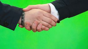 Handshake of two people. Close-up. Close-up of handshake of two unknown fellow man and woman against green wall background stock video footage