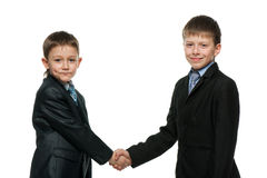 Handshake of two schoolboys Royalty Free Stock Image